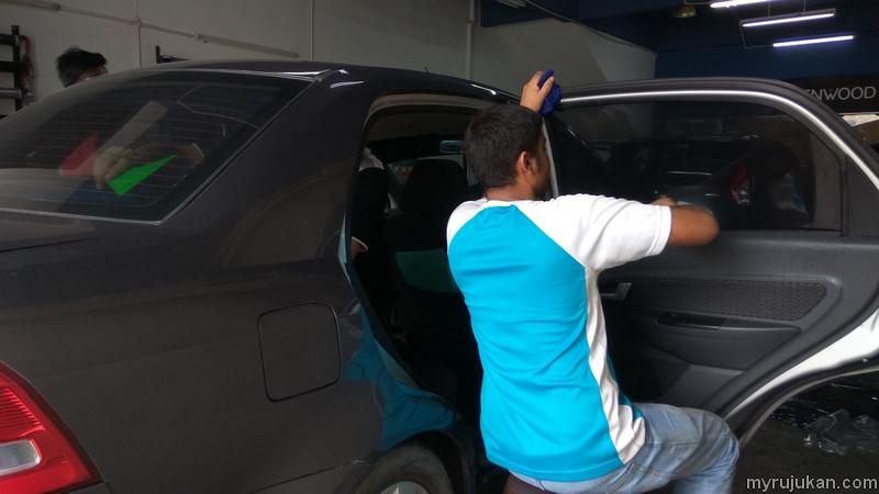 Pekerja sedang memasang tinted cermin kereta pada Proton Saga