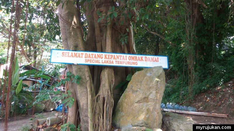 Papan tanda untuk masuk ke pantai ombak damai yang ada menjual laksa tempurung